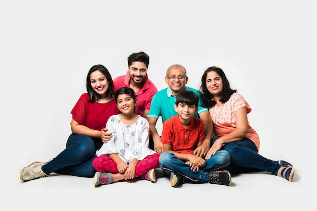 Crianças indianas com pais e avós, sentadas isoladas sobre um fundo branco, foto do estúdio