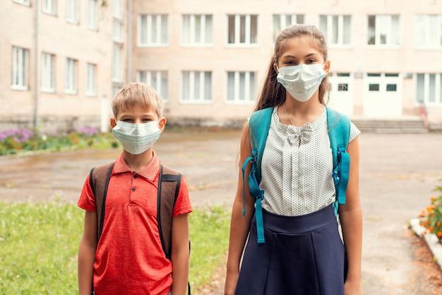 Crianças indo para a escola com uma máscara