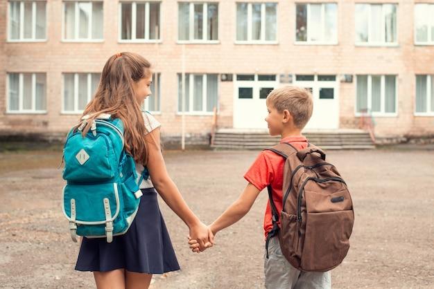 Crianças indo para a escola de mãos dadas