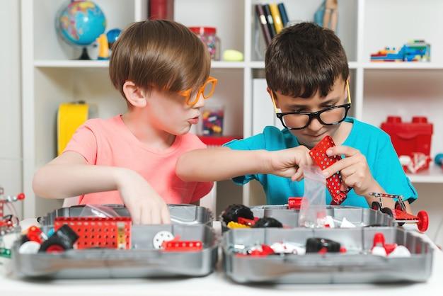Crianças inteligentes criando uma construção diy à mesa.