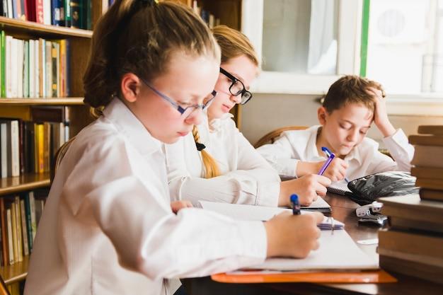 Crianças inteligentes, escrevendo sentado na biblioteca