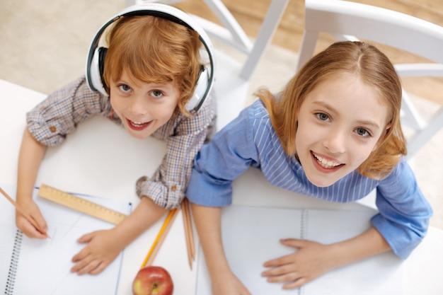 Crianças inteligentes vibrantes e brilhantes sentadas na mesa enquanto estudam em casa juntas e fazem algumas anotações em seus cadernos