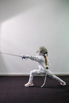 Crianças investem contra espadas. uma criança em uma classe em uma escola de esgrima