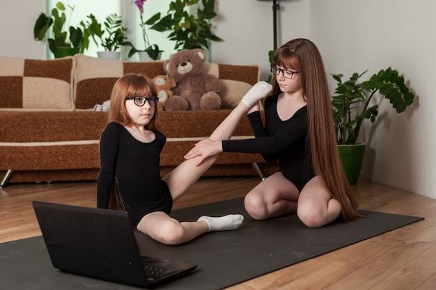 Crianças, irmãs, façam um treino em casa no tapete de ginástica.