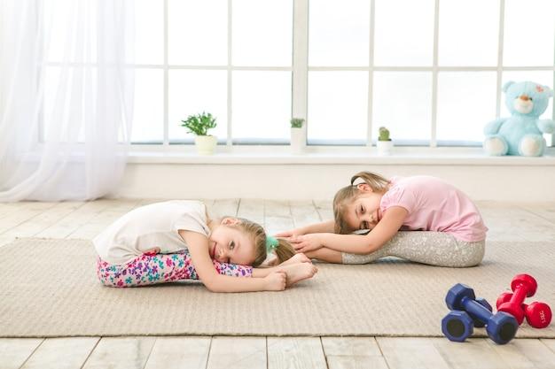 Crianças, irmãs, meninas, se exercitam juntas em ambientes fechados