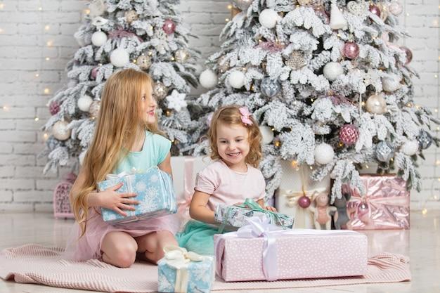 Crianças, irmãzinhas, com presentes felizes e elegantes no interior do natal