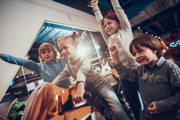 Crianças jogando jogo de corrida no centro de diversões