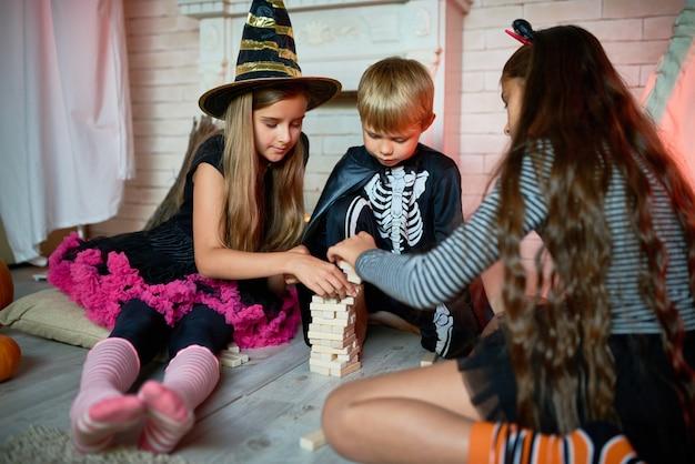 Crianças jogando jogos de tabuleiro na festa de halloween