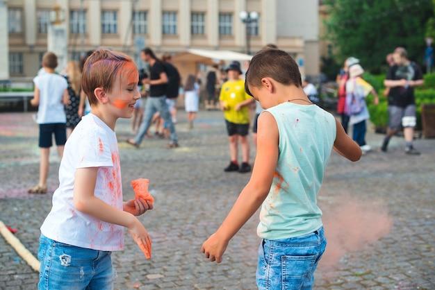 Crianças jogando pó colorido no ar. celebrações de holi. amigos se divertindo durante o holi fest.