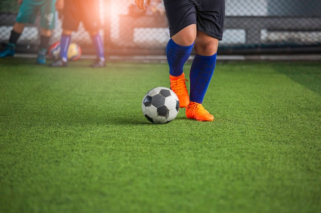 Crianças jogando táticas de bola de futebol de controle em campo de grama com fundo de treinamento.