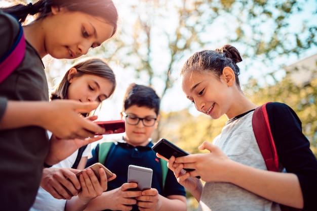 Crianças jogando videogame no telefone inteligente depois da escola