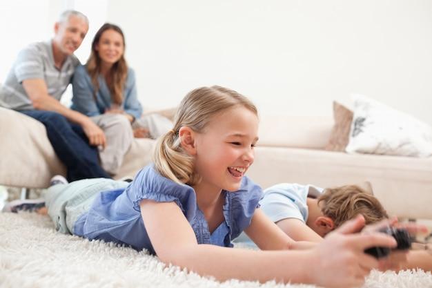 Crianças jogando videogames com seus pais no backgroun