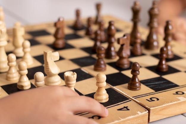 Crianças jogando xadrez de madeira, competição offline e conceito de estratégia