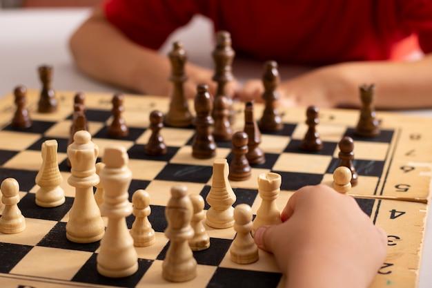 Crianças jogando xadrez em torneio de mesa entre crianças