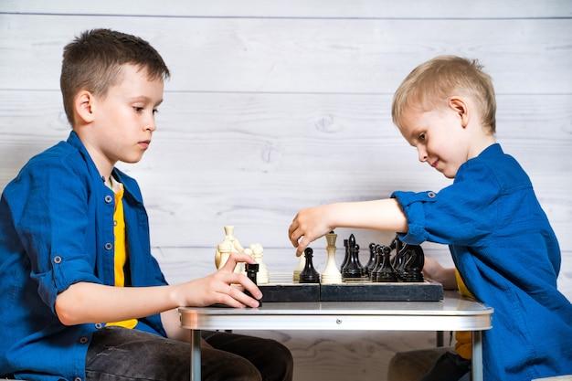 Crianças jogando xadrez na mesa. o conceito de infância e jogos de tabuleiro, desenvolvimento cerebral e lógica