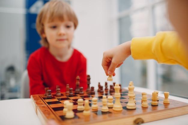 Crianças jogando xadrez no jardim de infância ou na escola primária.