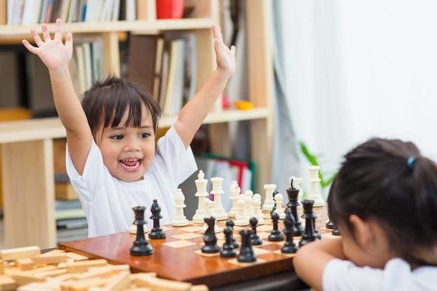 Crianças jogando xadrez - uma delas acaba de capturar um peão e comemora