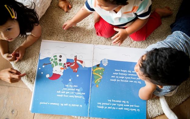 Crianças jovens lendo uma história de natal juntos