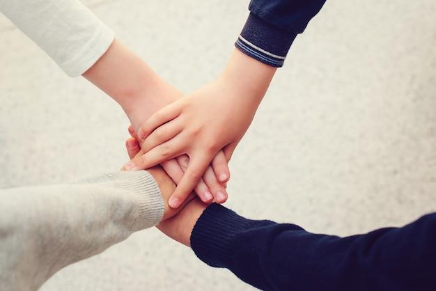 Crianças juntando as mãos, vista superior. conceito de unidade. grupo de amigos da escola com as mãos empilhadas uma em cima da outra.