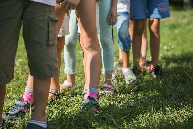 Crianças juntas em movimento do lado de fora e as pernas de alguma criança em ação na frente