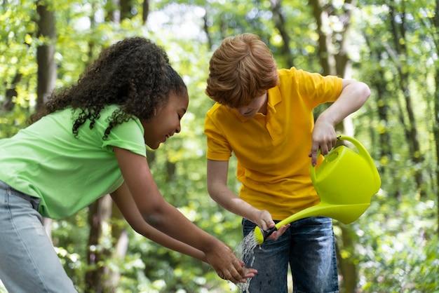 Crianças lavando as mãos após o plantio