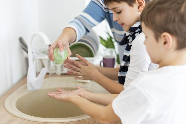 Crianças lavando as mãos com a ajuda da mãe