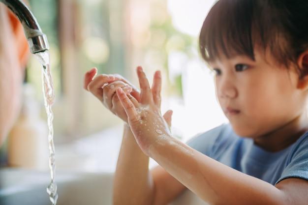 Crianças lavando as mãos para prevenção de infecção por coronavírus