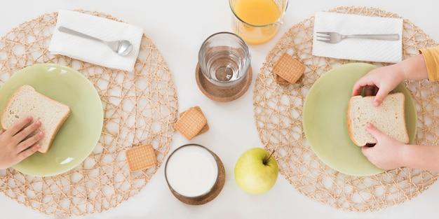 Crianças leigas planas tomando café da manhã