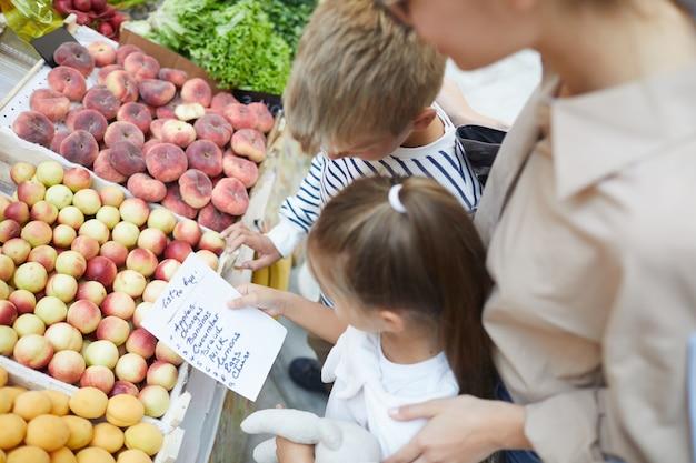 Crianças lendo a lista de compras no supermercado