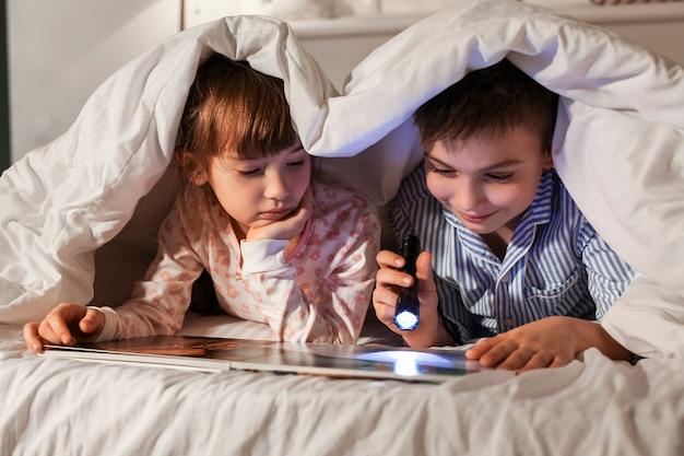 Crianças lendo histórias para dormir em casa