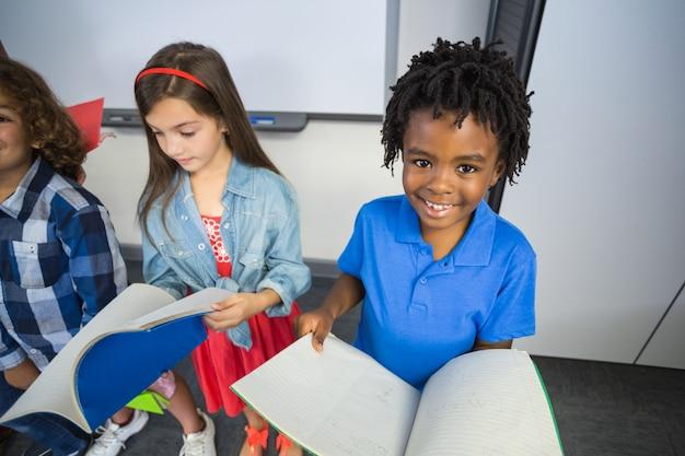 Crianças lendo livro em sala de aula