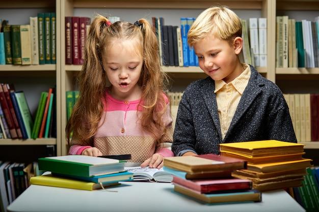 Crianças lendo livro juntas enquanto estão sentadas à mesa na biblioteca, menino e menina entre muitos livros, preparando-se para a escola