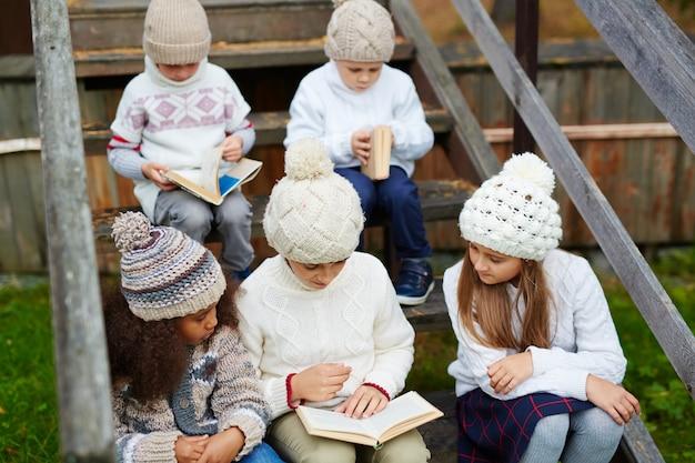 Crianças lendo livros ao ar livre