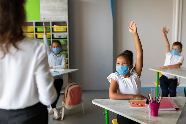 Crianças levantando as mãos para responder na aula