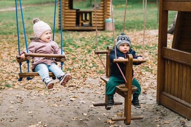 Crianças, ligado, balanços, em, pátio recreio