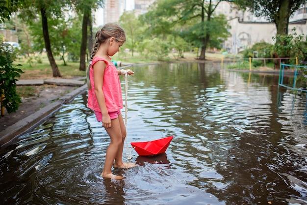 Crianças lindas brincando com barquinho de papel nas poças após a chuva quente de verão, infância feliz
