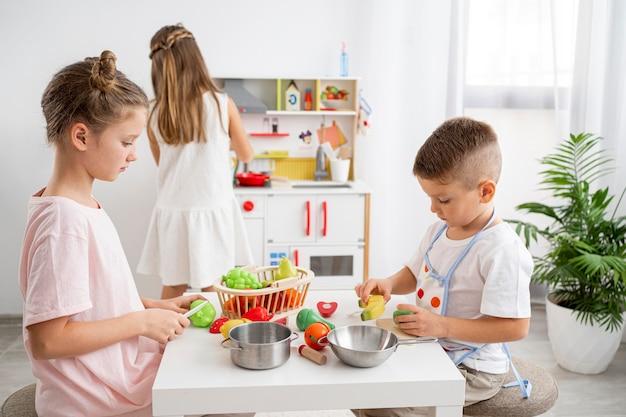 Crianças lindas brincando com um jogo de culinária