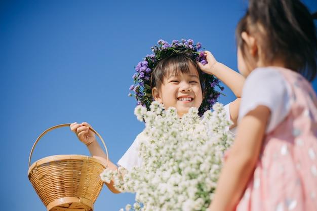 Crianças lindas e alegres brincando juntos no jardim de flores brancas