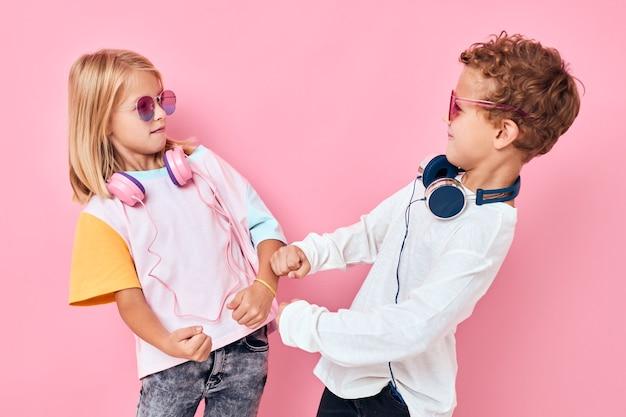 Crianças lindas e sorridentes em óculos de sol se divertem com amigos de fundo cor-de-rosa