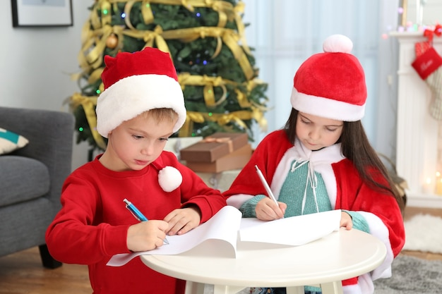 Crianças lindas escrevendo cartas para o papai noel na mesa