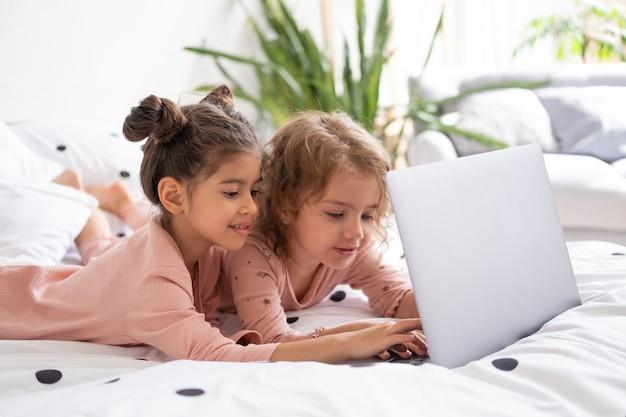 Crianças lindas garotinhas de pijama usando laptop na cama em casa crianças usando tecnologia
