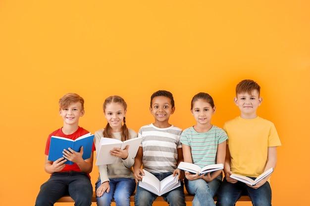 Crianças lindas lendo livros em uma superfície colorida