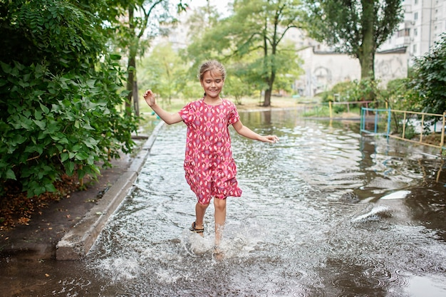 Crianças lindas pulando e nadando nas poças após a chuva quente de verão, infância feliz