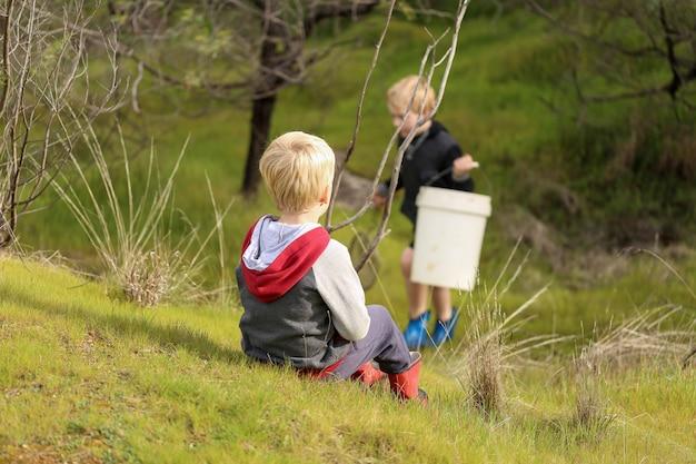 Crianças loiras se preparando para pegar peixes com uma rede de mão na natureza