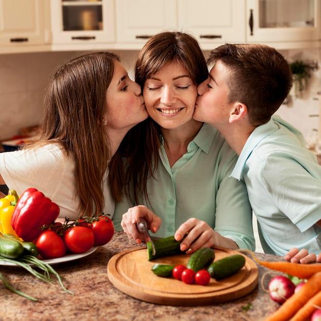Crianças, mãe a dar um beijo na cozinha enquanto prepara a comida