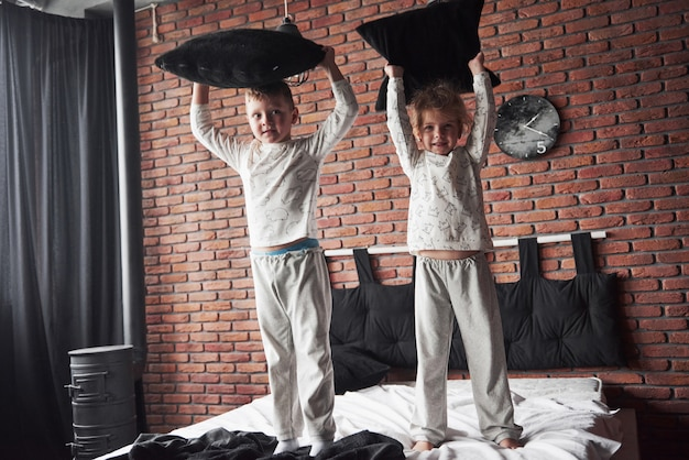 Crianças malcriadas menino e menina fizeram uma briga de almofadas na cama do quarto. eles gostam desse tipo de jogo