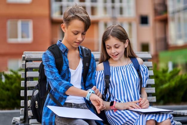 Crianças menina e menino sentado perto da escola e jogando smartwatch com livros e mochila.