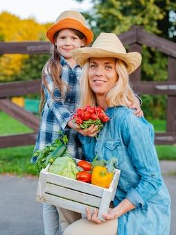 Crianças menina segurando a mãe uma cesta de legumes orgânicos frescos com o jardim em casa.
