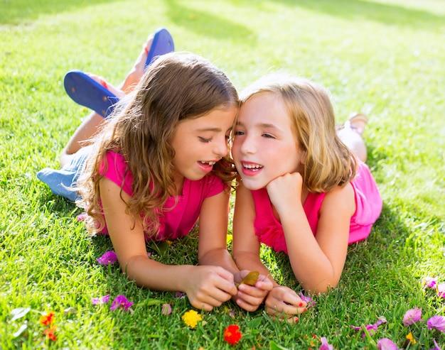 Crianças meninas brincando sussurrando na grama de flores