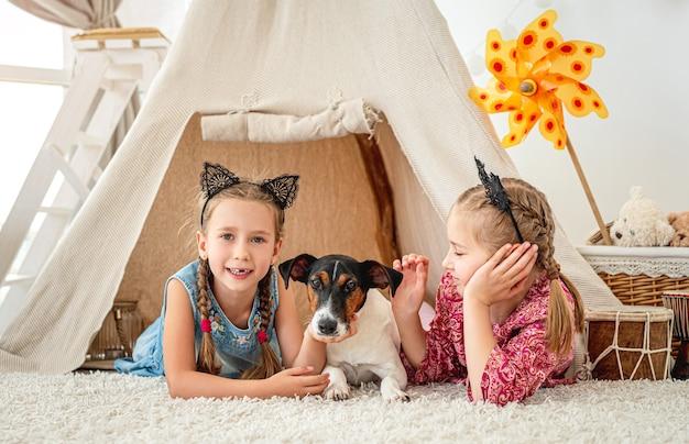 Crianças, meninas, deitadas com o cachorro fox terrier na cabana em casa